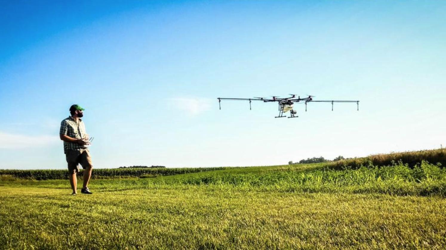 Mike Schmitz walks along side his Rantizo drone spraying crops